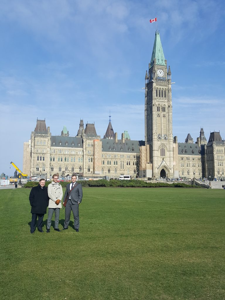 A photo - ARCH Executive Director Robert Lattanzio with Disability Law Intensive students  Cameron MacInnis  and Christopher McGoey in front of the building in the Parliament Hill